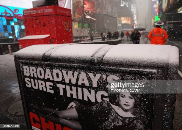 Workers in Times Square in New York March 21 2018 as the fourth nor'easter in a month hits the tristate area on the first full day of spring Winter...