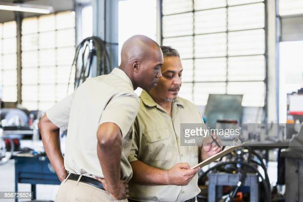 workers in truck repair shop - minority groups stock pictures, royalty-free photos & images