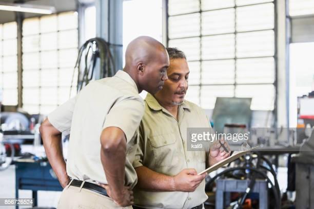 Workers in truck repair shop