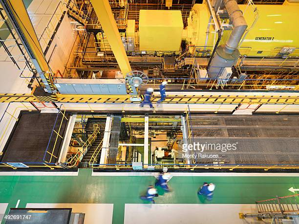workers in turbine hall of power station, high angle view - monty rakusen stock photos and pictures