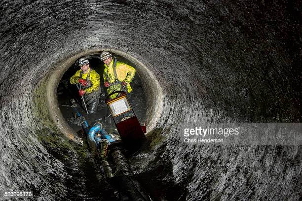 workers in underground polluted drainage pipe. - drain stock pictures, royalty-free photos & images