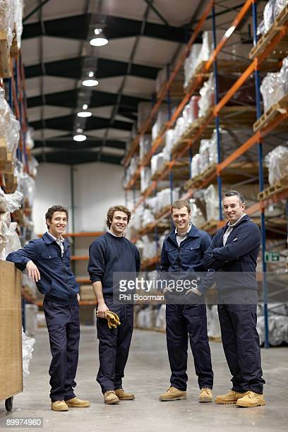 Workers in warehouse, smiling to camera