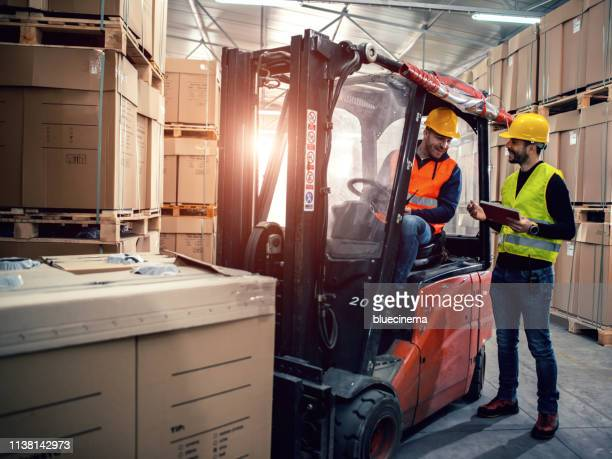 workers in warehouse with forklift - land vehicle stock photos and pictures