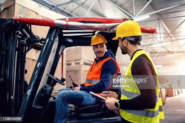 arbeiter im lager mit gabelstapler - gabelstapler stock-fotos und bilder