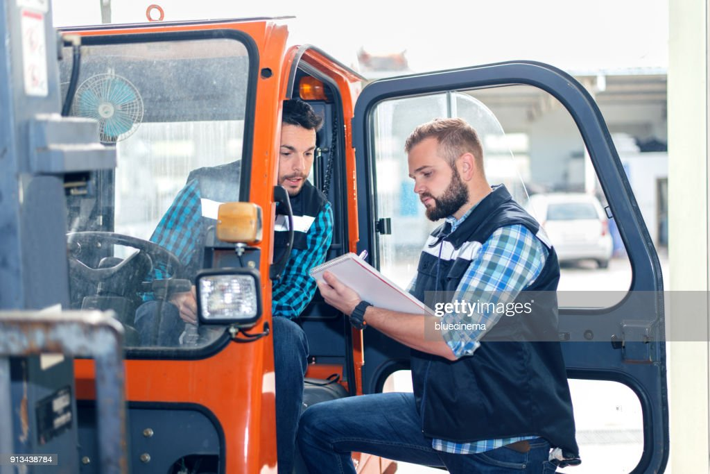 Workers in warehouse with forklift : Stock Photo