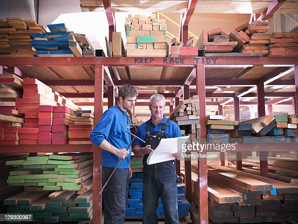 Workers in wood store in joinery