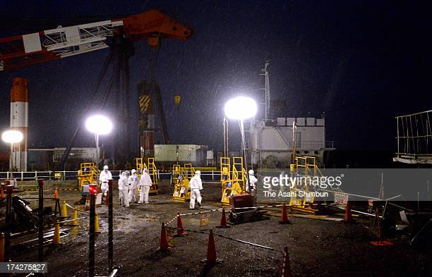 Workers inject a sealing agent into the ground to prevent potential leaks on the seaside of the Fukushima Daiichi nuclear power plant's No 2 reactor...