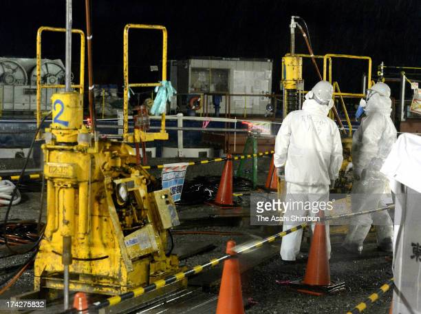 Workers inject a sealing agent into the ground to prevent potential leaks on the seaside of the Fukushima Daiichi nuclear power plant's No. 2 reactor...