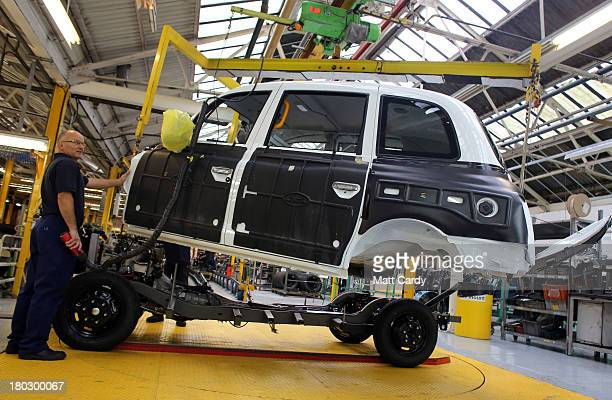 Workers inside the factory of The London Taxi Company attach the body of a TX4 London Taxi to its chassis on September 11 2013 in Coventry England...