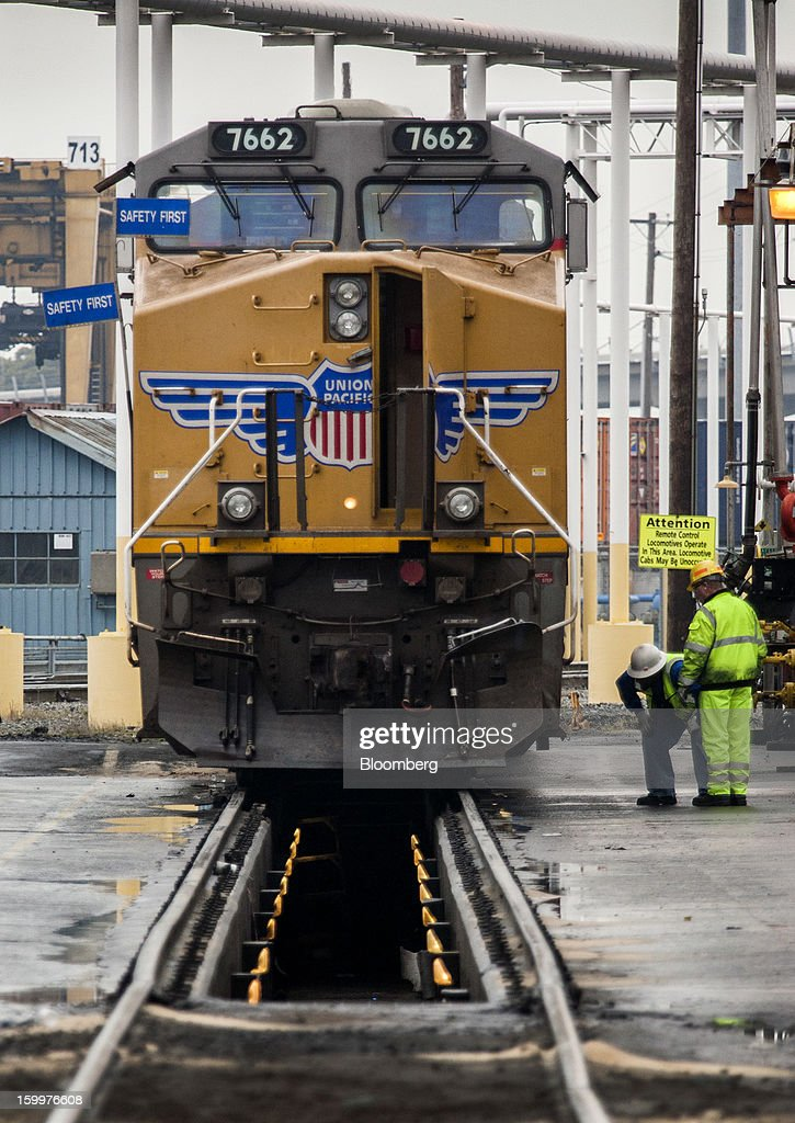 Workers inspect a freight locomotive at the Union Pacific Intermodal Terminal in Oakland, California U.S., on Wednesday, Jan. 23, 2013. Union Pacific Corp., the largest U.S. railroad by sales, posted higher fourth-quarter earnings than analysts estimated as shipments of chemicals and automobiles climbed. Photographer: Ken James/Bloomberg via Getty Images