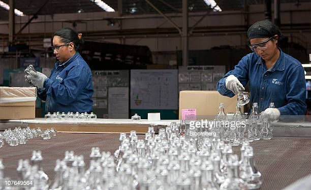 Workers inspect and package perfume bottles at glassmaker Vitro SAB's manufacturing plant in Toluca Mexico on Thursday Dec 16 2010 Vitro SAB the...