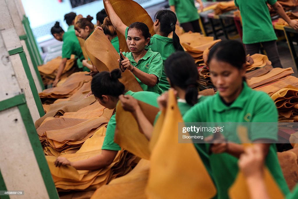 Workers inspect and trim smoked rubber sheets at the Thai Hua Rubber Pcl factory in Samnuktong, Rayong province, Thailand, on Wednesday, Jan. 29, 2014. Rubber production in Thailand, the world's largest exporter, may decline as growers from the main producing regions join protests seeking to overthrow the government, according to Von Bundit Co. Photographer: Dario Pignatelli/Bloomberg via Getty Images