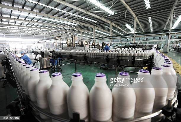 Workers inspect bottled beverages at a production line of the Bluesword Group's Drink And Food Industries on July 29, 2010 in Shifang of Sichuan...