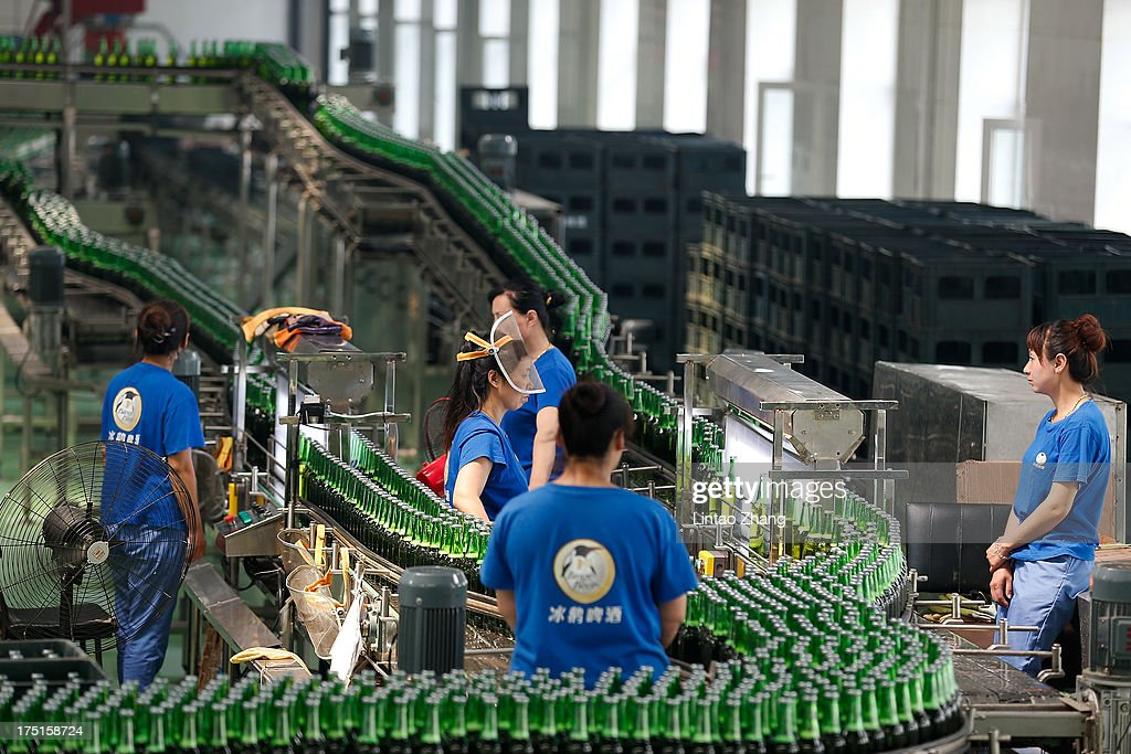 Workers inspect bottles of beer moving along a production line at the Jinzhu Manjiang beer factory on August 1, 2013 in Fujin, Heilongjiang Province, China. Recent significant sustained high temperatures in China are expected to push beer industry volume and revenue growth up significantly.