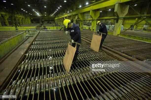 Workers inspect copper cathode sheets in an electrolytic tank inside the electrolysis shop at the MMC Norilsk Nickel PJSC copper refinery in Norilsk...