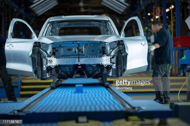 Workers inspect door fittings on unpainted Ford Focus automobile bodies inside a light tunnel at the Ford Motor Co. Factory in Saarlouis, Germany, on...