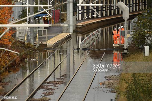 Workers inspect flooded rail tracks at Rotherham train station in Rotherham northern England on November 8 following flash flooding yesterday Over a...
