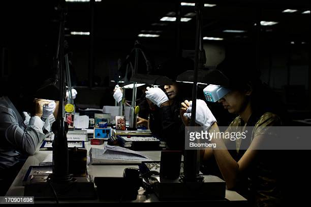 Workers inspect jewelry wearing magnifying goggles at the Kama Schachter Jewelry Pvt Ltd diamond studded gold and platinum manufacturing facility in...