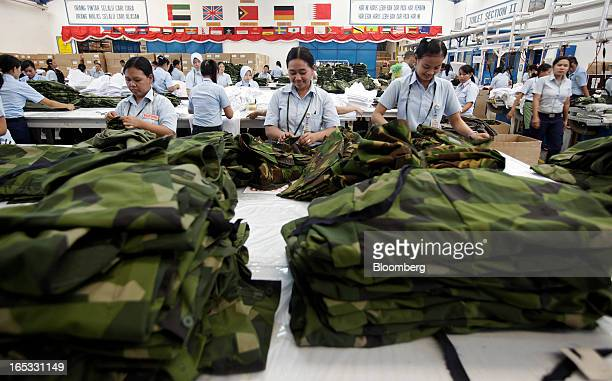 Workers inspect military combat uniforms on the production line in the garment area at a PT Sri Rejeki Isman factory in Sukoharjo Java Indonesia on...