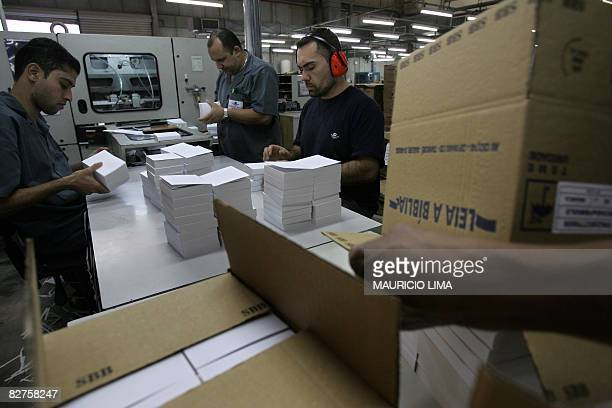 Workers inspect new pocket bibles ready for export in the production line of the Bible Society of Brazil factory, in Barueri, some 23 kilometres west...