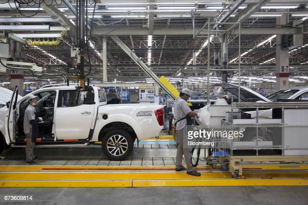 Workers inspect Nissan Motor Co Navara pickup trucks on an assembly line at the company's plant in Samut Prakan Thailand on Tuesday April 25 2017...