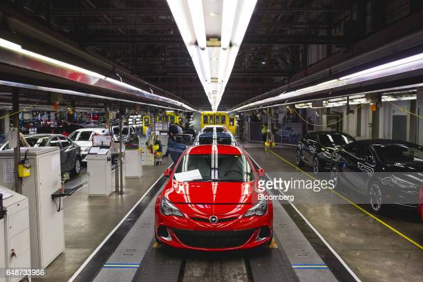 Workers inspect Opel Astra vehicles during quality control checks at the end of the production line at the Opel automobile plant in Gliwice Poland on...