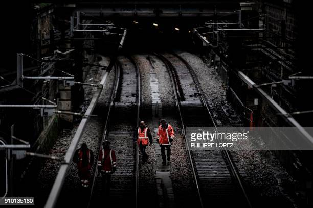 TOPSHOT Workers inspect railway tracks of the RER train near the river Seine in Paris on January 25 2018 The Seine continued to rise on January 25...
