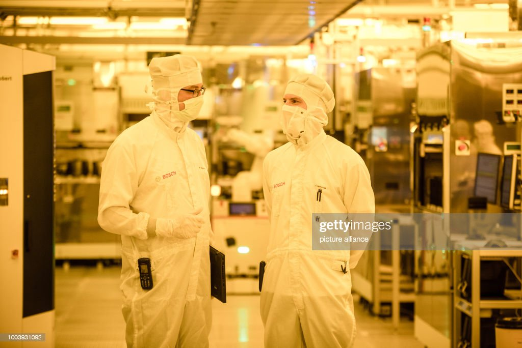 Workers inspect semiconductors in a wafer fab semiconductor