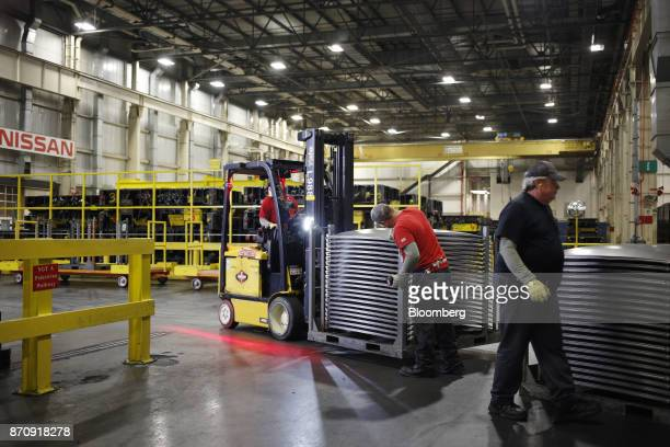 Workers inspect stacks of vehicle hoods for quality at the stamping plant of the Nissan Motor Co manufacturing facility in Smyrna Tennessee US on...