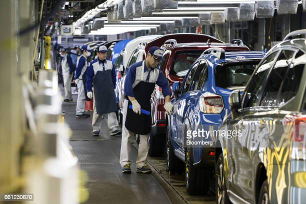 Workers inspect Subaru branded vehicles on the production line of Fuji Heavy Industries Ltd's Gunma Yajima Plant in Ota Gunma Japan on Thursday March...
