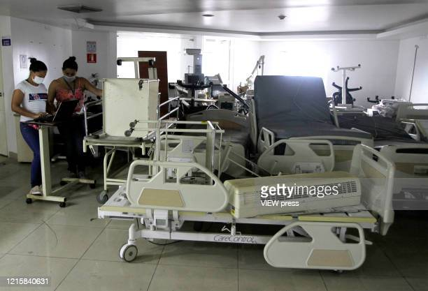 Workers inspect the abandoned hospital of Saludcoop in Medellín Colombia on March 29 2020 The cleaning and adaptation works began to enable an...