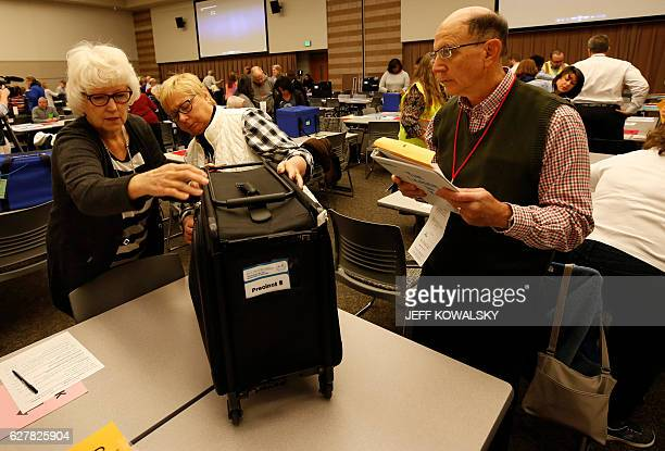 Workers inspect the container before the start of the recount of ballots cast in Oakland County Michigan from the 2016 US presidential race to be...
