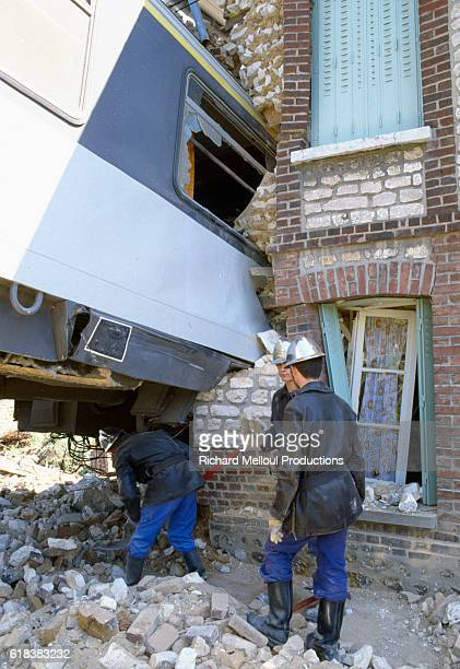 Workers inspect the damage caused after a train jumped the tracks and smashed into a building in St. Pierre-du-Vauvray, France. Nine people were...