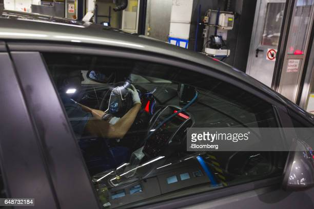 Workers inspect the interior systems of an Opel Astra automobile during quality control checks at the end of the production line at the Opel...