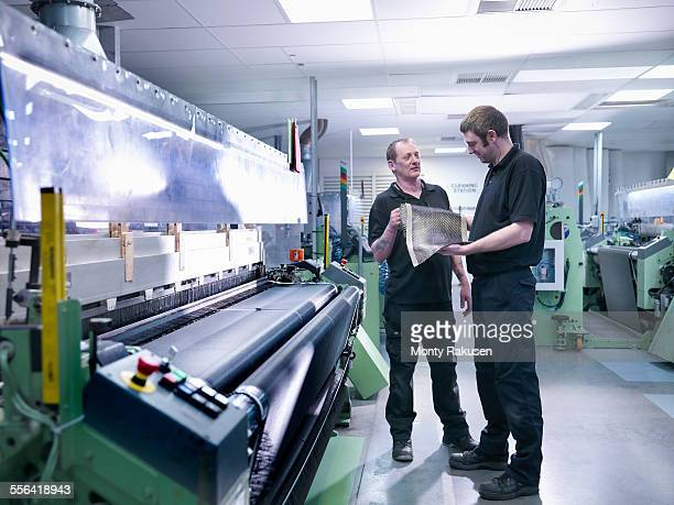 Workers inspecting carbon fibre sample in carbon fibre factory