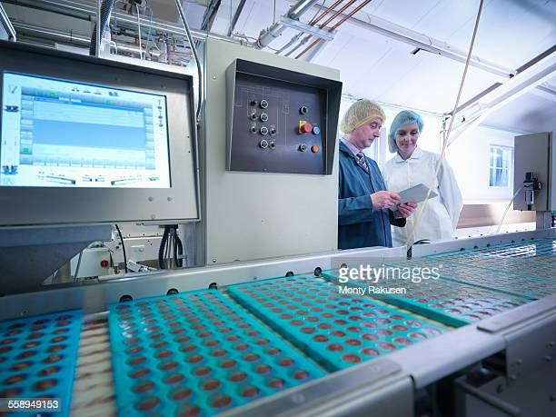 workers inspecting chocolates in moulds in chocolate factory - chocolate factory stock pictures, royalty-free photos & images