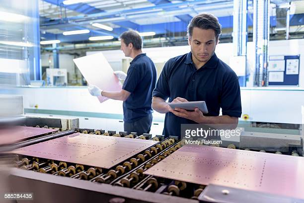 Workers inspecting circuit board during manufacture in circuit board factory