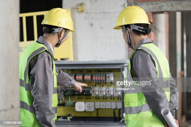 workers inspecting distribution boxes - electrical box stock pictures, royalty-free photos & images