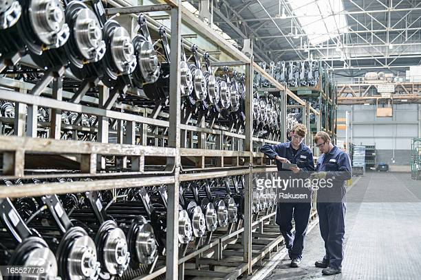 Workers inspecting large number of axles on shelving unit in car plant