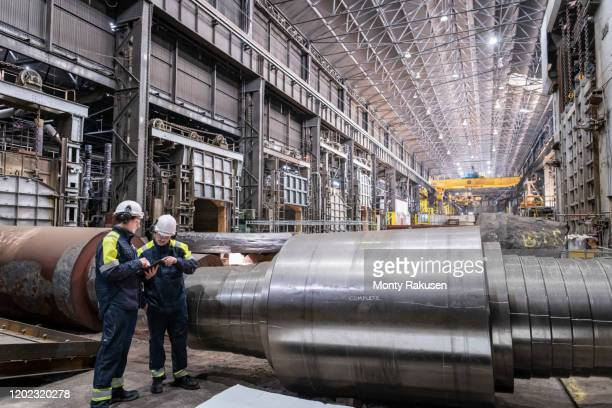workers inspecting large steel roller in forge of steelworks - industry stock pictures, royalty-free photos & images