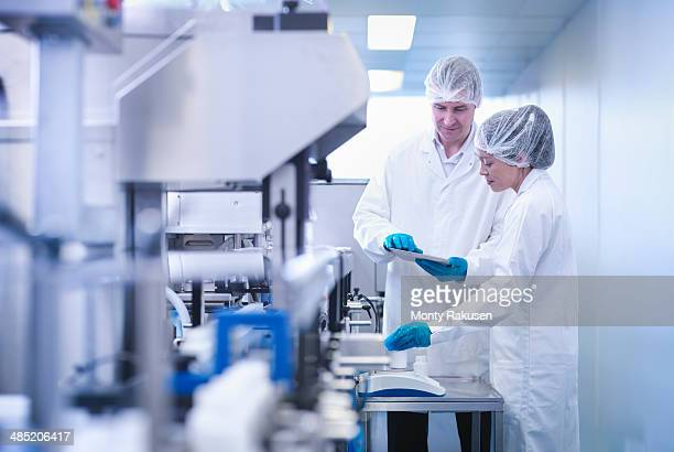 Workers inspecting product in pharmaceutical factory