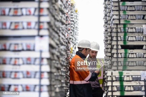 Workers inspecting stacks of aluminium ingots in warehouse