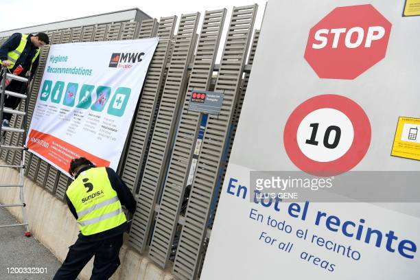 Workers install a banner with hygiene recommendations outside the Mobile World Congress MWC venue on February 12 2020 at the Fira Barcelona Montjuic...