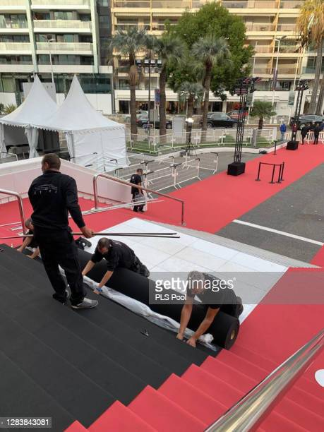 Workers install a black carpet at Palais des Festivals on October 29, 2020 in Cannes, France. Cannes Film Festival pays a tribute to Nice attack...