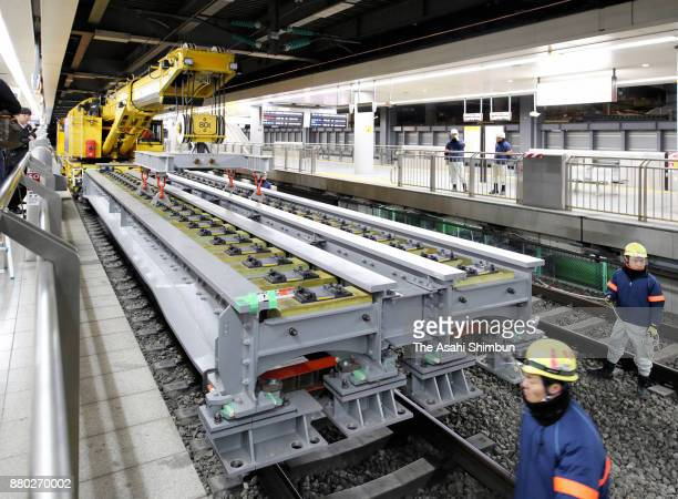 Workers install a bridge beam after pebbles were removed from under the Tokaido Shinkansen Line rail tracks in preparation for the construction of a...