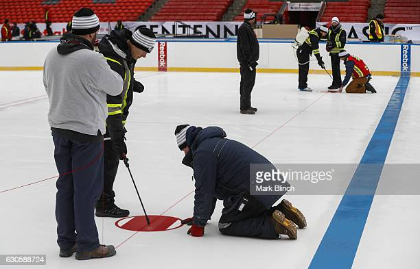 Workers install a face off circle during the build out of the outdoor rink for the 2017 Scotiabank NHL Centennial Classic between the Detroit Red...
