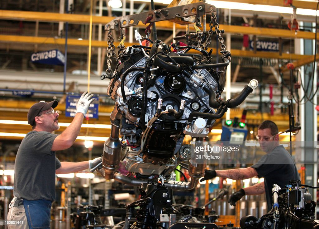 Workers Install A Ford EcoBoost Engine Into 2014 F150 Truck Chassis On The Assembly Line
