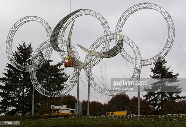Workers install a giant illuminated Paralympic symbol in place of the Olympic Rings as you leave Vancouver International Airport. The symbol of the...