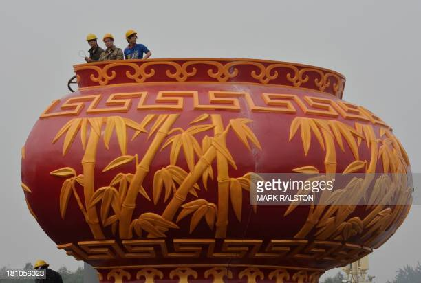 Workers install a giant vase as part of the upcoming Chinese National Day celebrations at Tiananmen Square in Beijing on September 19 2013 The...