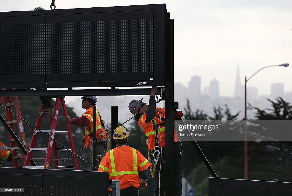 Workers install a new LED sign onto the top of the Golden Gate Bridge toll plaza on March 25, 2013 in San Francisco, California. Workers are making last minute changes to the Golden Gate Bridge toll plaza in preparation of making the iconic bridge the first major toll bridge in the nation to go to all electronic tollbooths. The entire staff of full time toll collectors will be replaced by the automated booths starting on March 27.